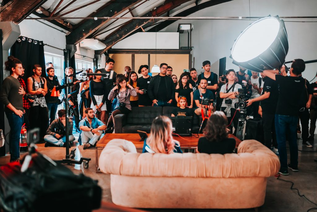 Gorilla Jobs Blog Avoid Interview Bias Group of People Behind Camera Arranging Interview For Two People On Couch