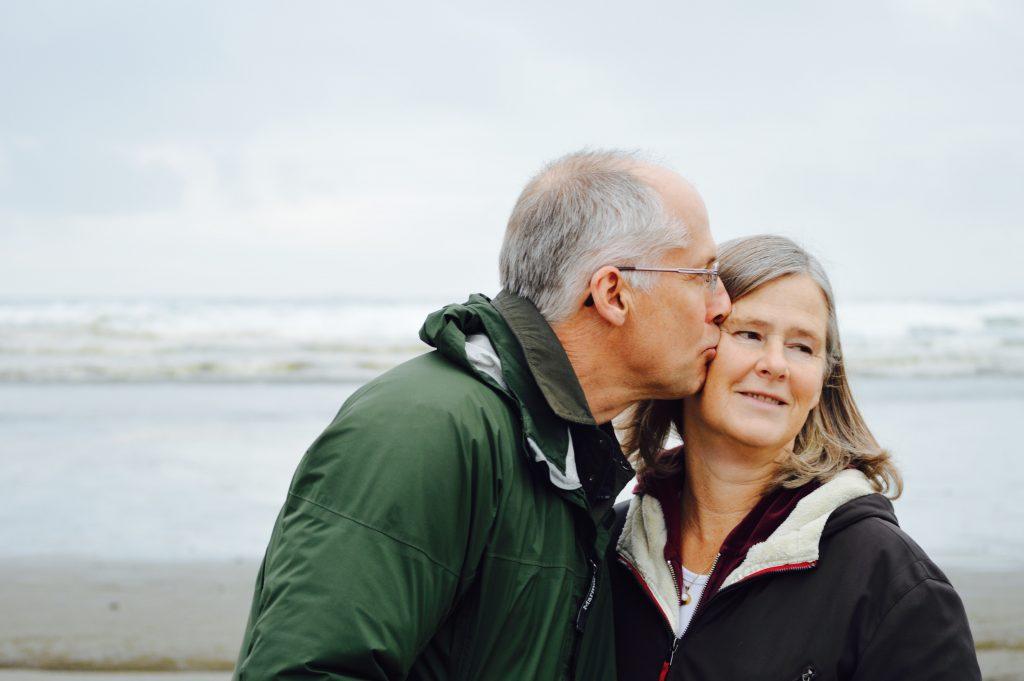 Gorilla Jobs Blog Aged Care Recruitment Elderly Couple On A Beach Husband Kisses Wife On Cheek
